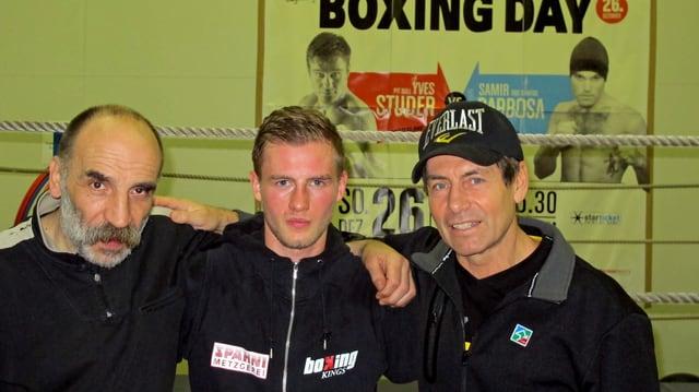 Die beiden Trainer Bruno Arati und Daniel Hartmann posieren mit ihrem Schützling Alain Chervet im Boxkeller.