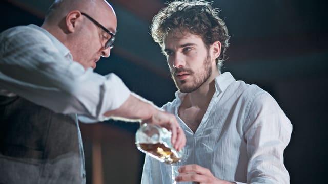 Schauspieler (Vater) schenkt Schauspieler (Sohn) einen Whiskey ein