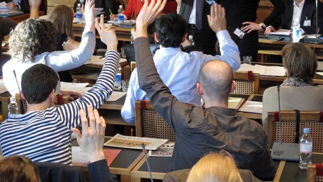 Personen stimmen per Handerheben ab.