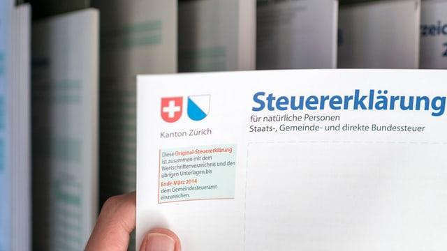 Eine Person hält eine Steuererklärung des Kantons Zürich in den Händen