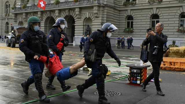 Polizisten tragen eine Person davon.