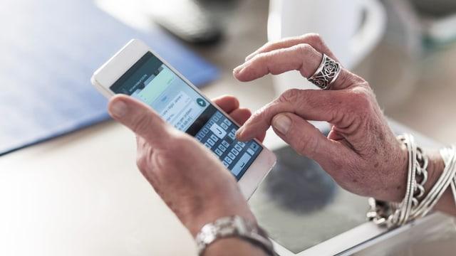 Zwei ältere, reichgeschmückte  Frauenhände halten ein Smartphone.