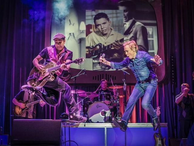 Ein Sänger und ein Gitarrist auf einer Konzertbühne.