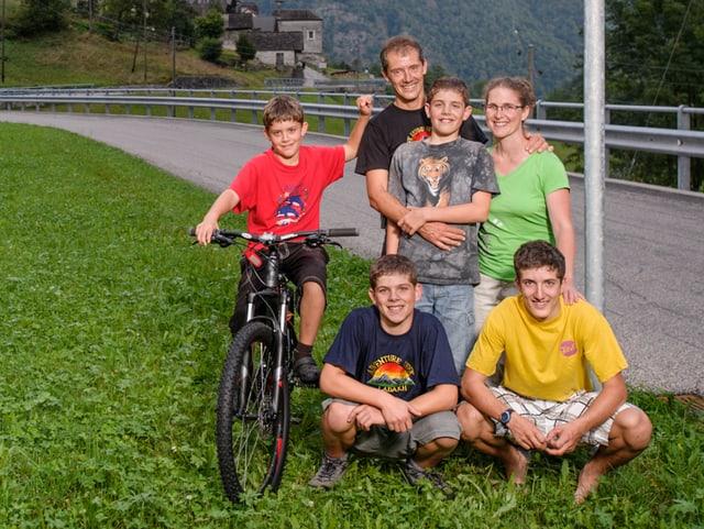 Die sechsköpfige Familie Ambrosini steht gemeinsam auf einer Wiese am Strassenrand.