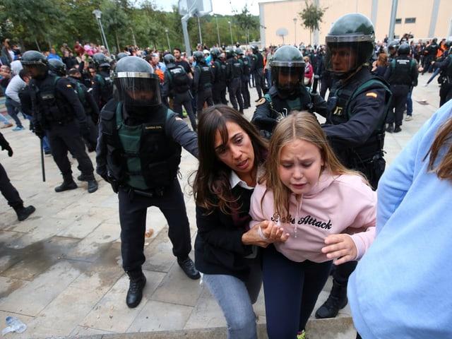 Frau mit Kind werden von Nationalpolizisten auf die Seite gewiesen.