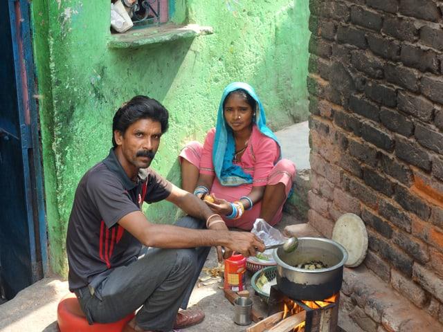 Ein Mann und eine Frau sitzen vor einem Kochherd mit offenem Feuer.