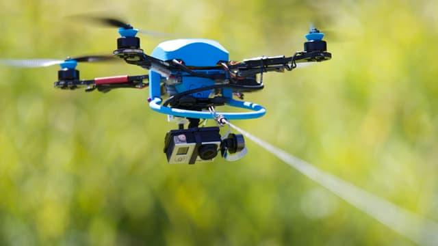 Ein Quadrocopter fliegt im Freien an einer Leine.