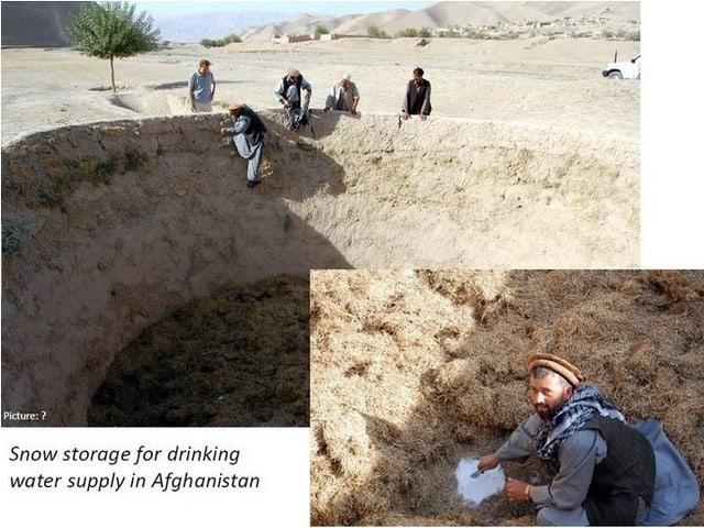 Grosses leeres Loch in einer wüstenähnlichen Landschaft. Am Rand sitzen Afghanen, eine Person klettert hinunter.