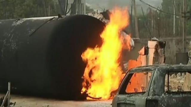 Ein Gastankwagen brennt, im Vordergrund ein Auto