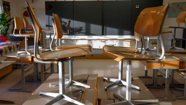 Blick in ein Klassenzimmer, in welchem die Stühle auf die Tische gestellt sind.