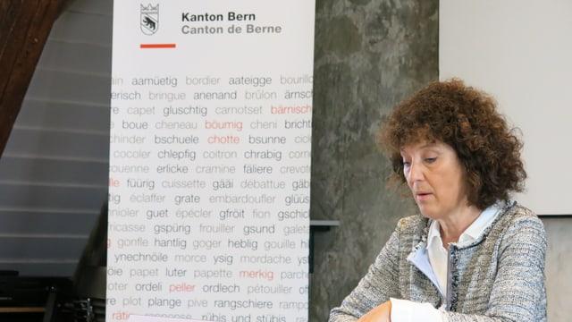 Barbara Egger sitzt an einem Pult und spricht, vor einem Plakat mit dem Schriftzug «Kanton Bern».