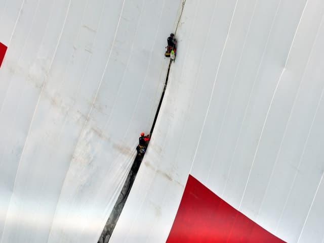 Mit Seilen und Spannsets flicken die Höhenarbeiter die Schweizerfahne am Berg.