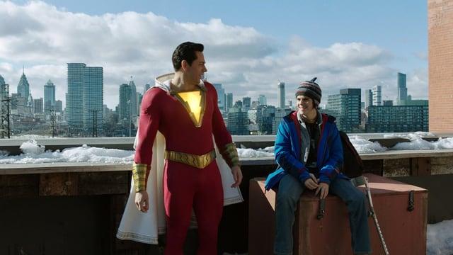 Superheld Shazam und Teenager Freddy auf dem Dach eines Hochhauses.