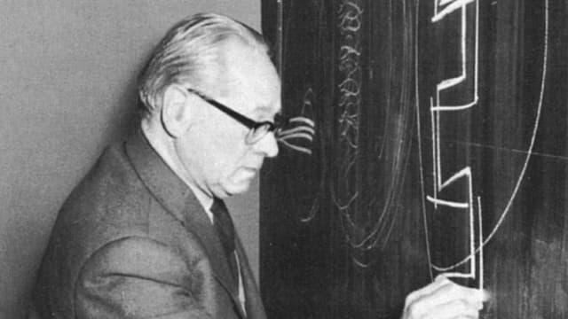 Ein mann kritzelt mit Kreide Formen auf eine Wandtafel.