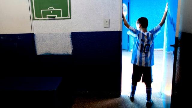 Ein Junge im Fussballtenue (Messi-T-Shirt) steht in einem Türrahmen, links an der Wand ein aufgemaltes Fussballfeld.