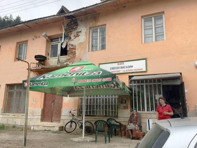 Sonnenschirm und Plastikstühle vor dem Dorfladen in Potop.
