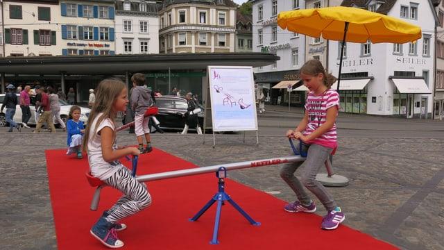 Zwei Mädchen auf einer Schaukel auf einem roten Tepich auf dem Basler Barfüsserplatz.