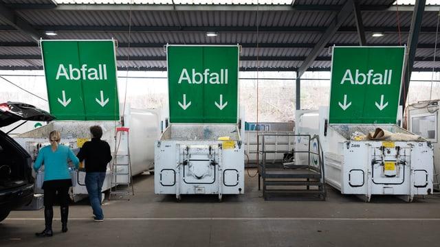 Drei grosse grüne Schilder mit Aufschrift Abfall über Containern.