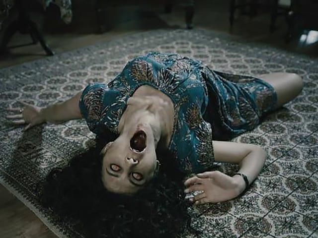 FIlmstill aus einem Horrorfilm: Eine Frau wälzt sich am Boden.