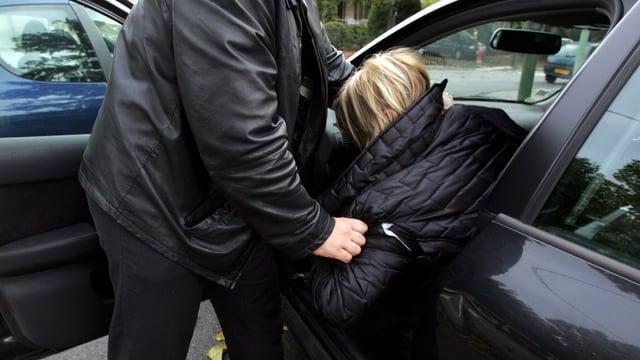 Mann zerrt Frau aus einem Auto