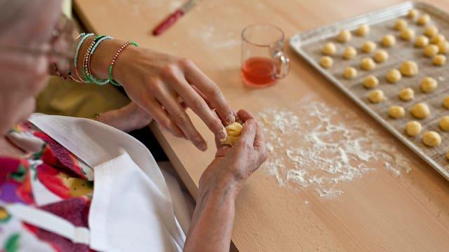 Das Domicil Bethlehemacker in Bern, Schweiz. Bewohnerin formt Bälle aus Teig um Kekse zu machen. Fotografiert am 18. Oktober 2012.