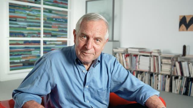 Ein Mann in blauem Hemd und mit grauen Haaren sitzt in einem Büroraum.