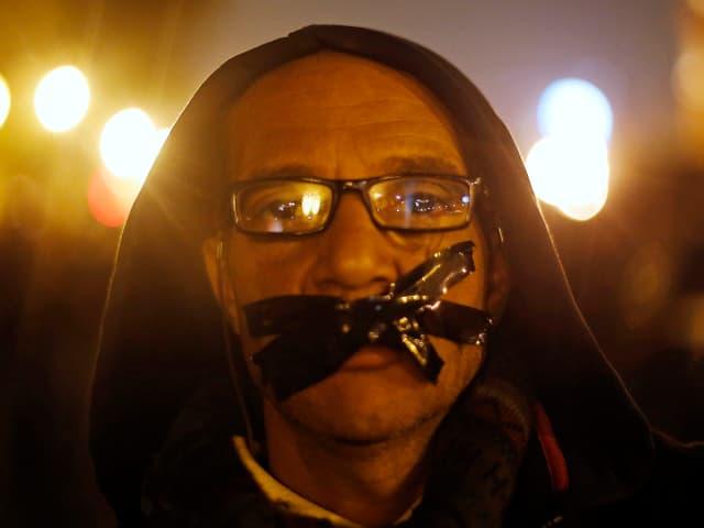 Protestierender mit symbolischem Klebstreifen vor dem Mund