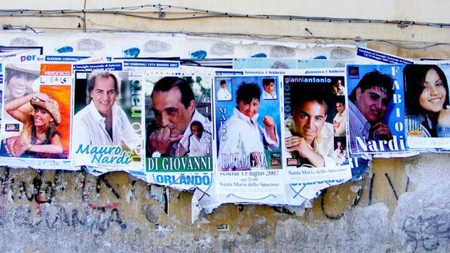 Plakate an einer Mauer.