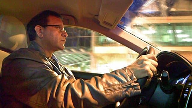 Einwanderer Raiz Hussain aus Pakistan am Steuer seines Taxis