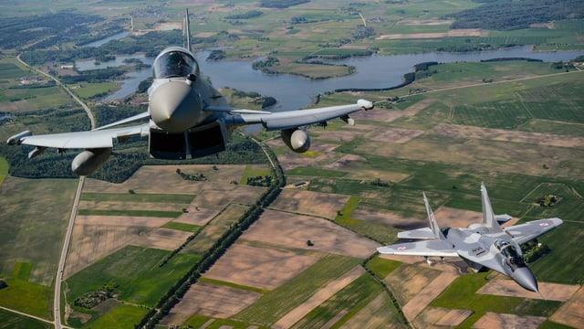 Zwei Kampfjets – ein britischer und ein polnischer – überfliegen ländliches Gebiet in Litauen.