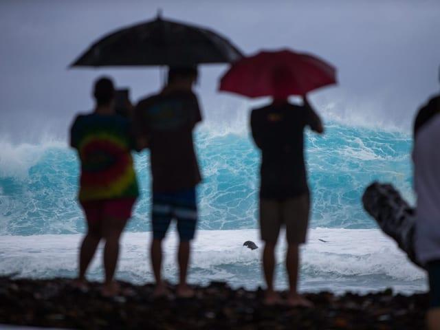 Einheimische beobachten das Sturmtreiben am Strand.