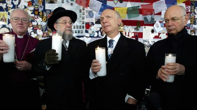 Vier Männer halten je eine Kerze in der Hand.