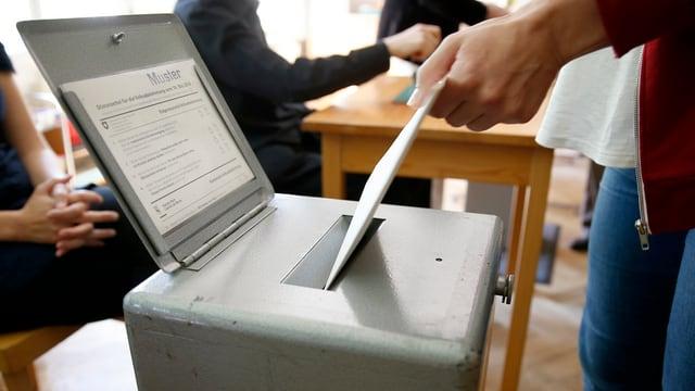 Eine Person wirft das Wahlcouvert in eine Wahlurne.