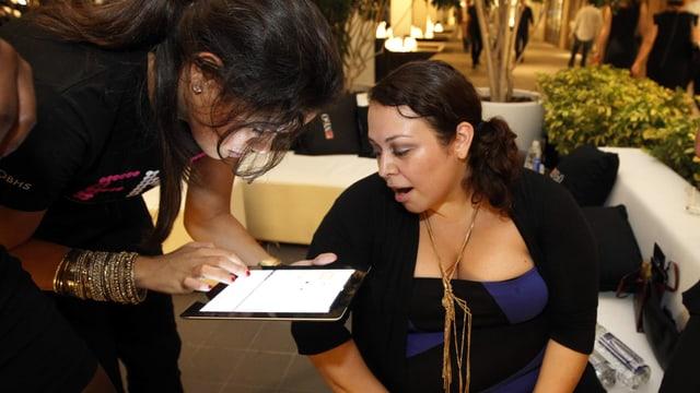 Eine Frau mit einem Tablet-Computer in der Hand beugt sich zu einer ihr rechts gegenübersitzenden Frau hinunter.