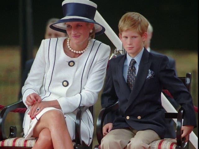 Diana und Prinz Harry sitzen nebeneinander auf einem Stuhl.