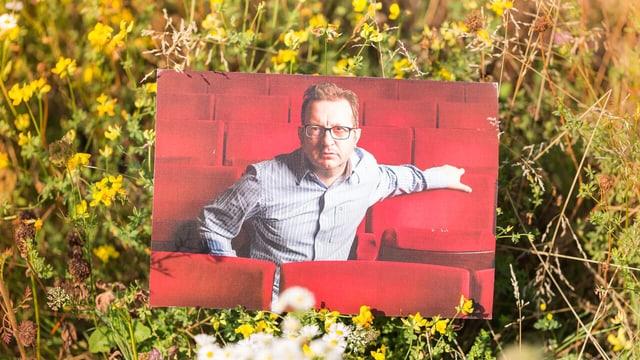 Im Gras einer Blumenwiese steckt ein Foto. Es zeigt einen Mann inmitten roter Konzertbestuhlung.