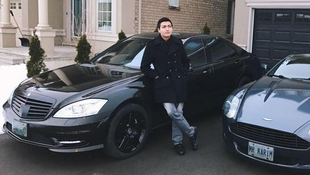 Junger Mann vor zwei Luxus-Autos.
