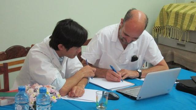 Ein asiatischer und ein westeuropäischer Arzt sitzen an einem Tisch und arbeiten zusammen