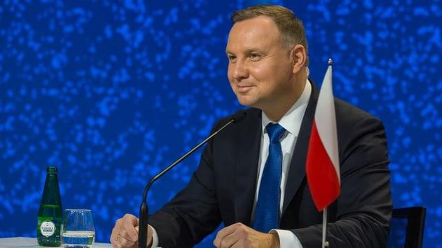 Andrzej Duda sitzend neben einer kleinen polnischen Flagge und Mikrofonen.