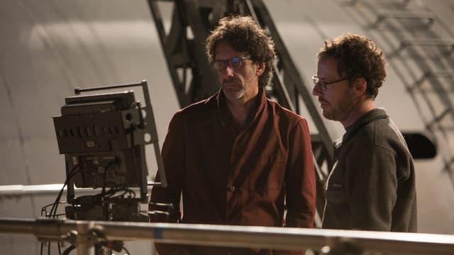 Joel und Ethan Coen, stehend auf einen Bildschirm schauend.