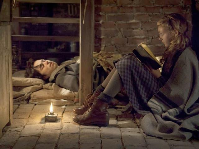 Mädchen sitzt auf Kellerfussboden und liest krankem Mann, der ebenfalls auf dem Boden liegt, aus einem Buch vor.
