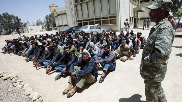 Flüchtlinge sitzen auf dem Boden, bewacht von einem Soldaten.