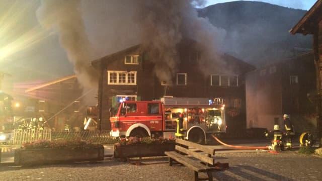 Feuerwehrauto vor dem Haus, aus dem Rauch dringt.