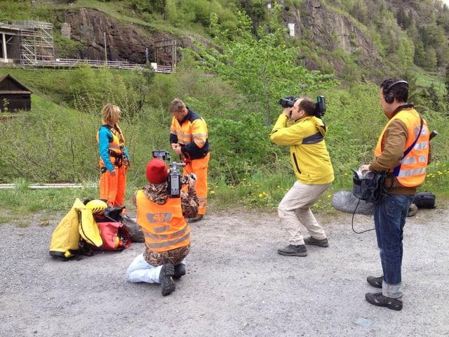 Zwei Kameraleute, ein Tonoperateur, eine Moderatorin und ein Bergführer stehen mit gelben und orangen Warnkleidern auf einem Platz. Die Kameraleute sind am Filmen.