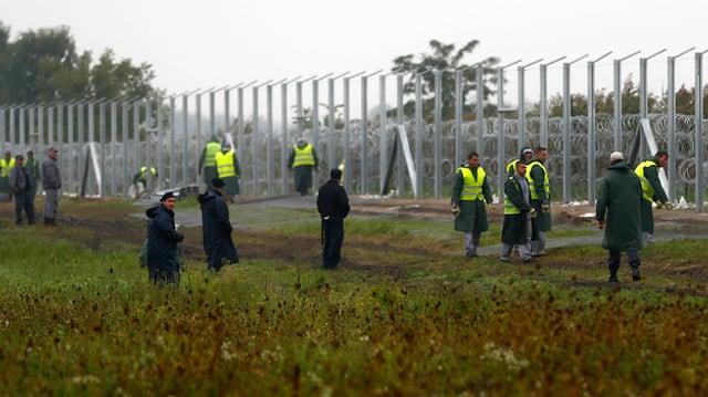 Uniformierte bewachen den Grenzzaun.