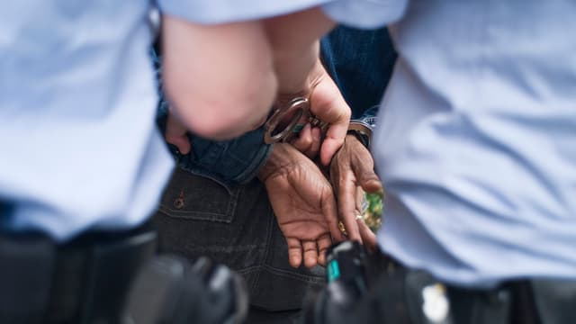 Hände einer schwarzen Person in handschellen