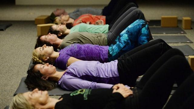 Yogapraktizierende liegen in einer Reihe auf dem Rücken und entspannen sich