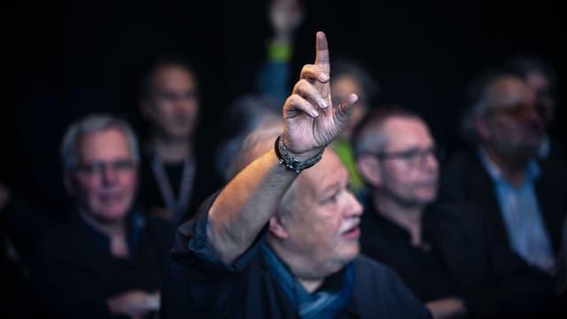 Ein Mann streckt seinen Arm aus und will in einer Diskussion etwas sagen.