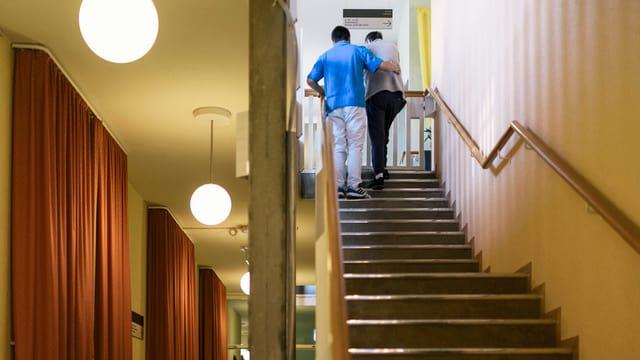 EIn Mann hilft einer Frau die Treppe hoch.