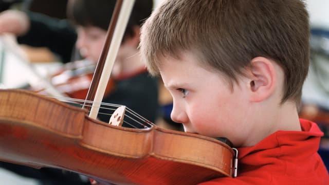 Ein Bub mit rotem Pullover spielt Geige. Er ist von der Seite her fotografiert.